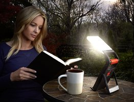 woman reading a book on the backyeard with an Energizer folding lantern on the table