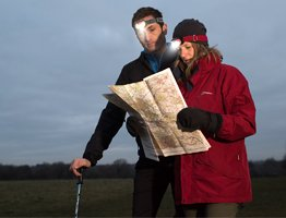 couple wearing energizer headlamp and reading a map