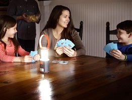 mom playing cards with kids in the dark with an Energizer area lantern on the table